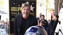 """Pemeran Luke Skywalker dalam film """"Star Wars"""", Mark Hamill berpose dengan karakter droid R2-D2 saat upacara pemberian Hollywood Walk of Fame di Los Angeles (8/3). (Jordan Strauss / Invision / AP)"""