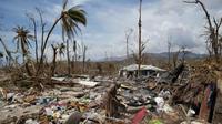 Seorang perempuan berjalan di antara reruntuhan yang disebabkan terjangan badai Matthew (Reuters)