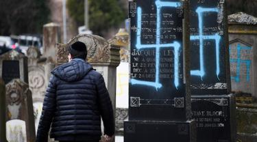 Seorang pria berjalan melewati makam Yahudi yang dicoret simbol Nazi di pemakaman Yahudi, Quatzenheim, Prancis, Selasa (19/2). Aksi vandalisme ini dilakukan terhadap sekitar 80 makam. (Frederick FLORIN/AFP)