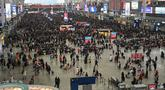 Penumpang menunggu jadwal keberangkatan mereka di Stasiun Kereta Hongqiao di Shanghai pada Senin (20/1/2020). China berada di tengah-tengah kesibukan migrasi manusia tahunan ketika jutaan orang pulang ke kampung halaman mereka untuk menikmati libur Tahun Baru Imlek. (HECTOR RETAMAL/AFP)