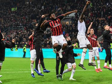 Gelandang AC Milan, Franck Kessie (tengah) dan rekan setimnya merayakan kemenangan bersama suporter usai pertandingan melawan Lazio pada lanjutan Liga Serie A Italia di stadion San Siro (13/4). Milan menang tipis 1-0 atas Lazio berkat gol penalti Kessie. (AFP Photo/Miguel Medina)