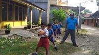 Siswa mengikuti pemanasan dengan bermain bola tangan pada jam pelajaran olahraga. (Foto : Felek Wahyu/Liputan6.com)