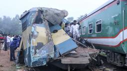 Orang-orang berdiri di gerbong kereta yang rusak parah setelah dua kereta yang melaju bertabrakan di distrik Brahmanbaria, 82 kilometer (51 mil) timur ibukota, Dhaka, Bangladesh, Selasa (12/11/2019). Sekitar 16 orang tewas dan 60 lainnya terluka akibat kecelakaan tersebut. (AFP Photo/STR)