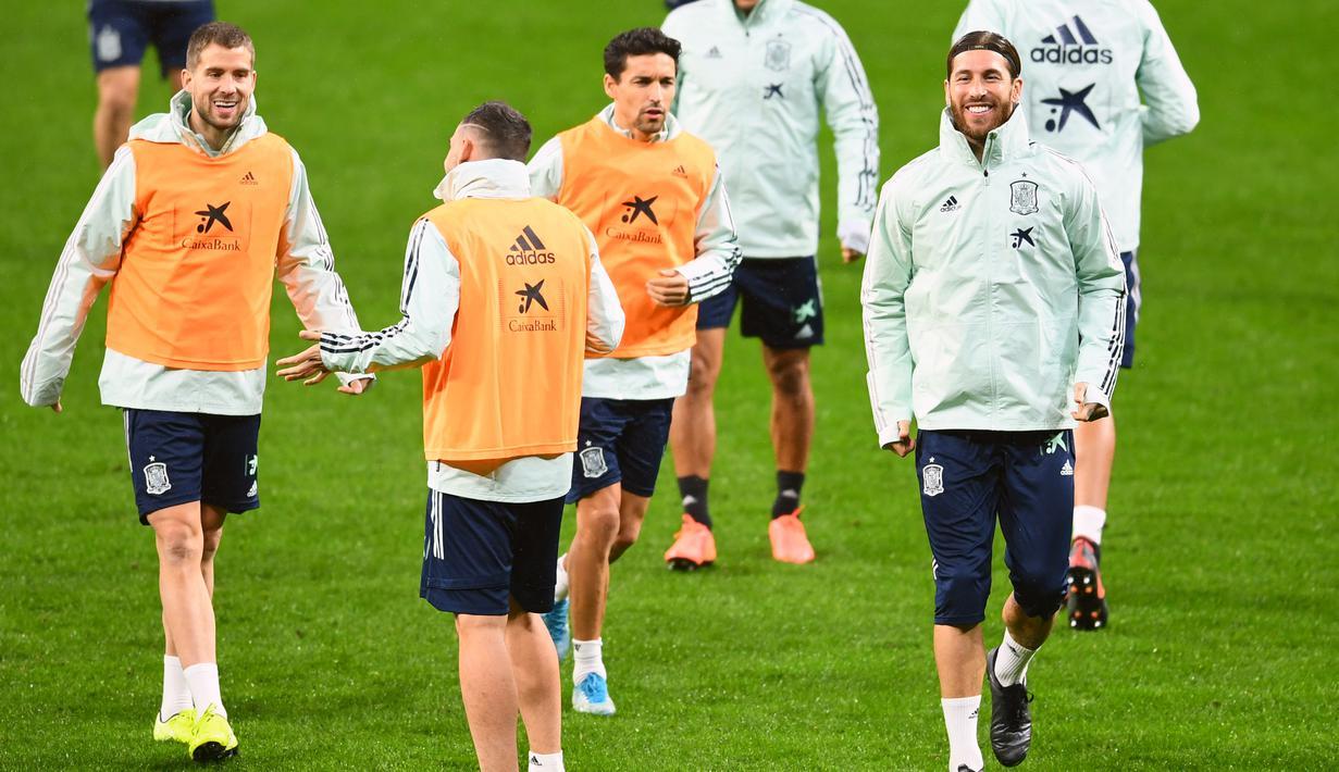 Bek Spanyol Sergio Ramos (kanan) tersenyum saat melakukan pemanasan selama sesi latihant tim di Stadion Wanda Metropolitano di Madrid (17/11/2019). Spanyol akan bertanding melawan Rumania pada Grup F Kualifikasi Piala Eropa 2020. (AFP Photo/Gabriel Bouys)