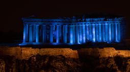 Situs warisan dunia Kuil Parthenon berwarna biru saat Hari Anak Sedunia, Athena, Yunani, Rabu (20/11/2019). Nuansa biru pada kuil yang berada di puncak bukit Acropolis tersebut untuk memperingati Hari Anak Sedunia yang jatuh setiap tanggal 20 November. (AP Photo/Petros Giannakouris)