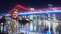 Yogi menggunakan baju khas Jawa pada Senin malam sambil mengabadikan momen bersejarah dengan jembatan Brisbane yang berwarna merah putih. (Facebook. Agustinus Jogiono)