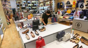 Karyawan tenant membersihkan meja display sepatu dan tas di Lippo Mall Puri, Jakarta, Rabu (3/6/2020). Menuju new normal Lippo Malls Indonesia (LMI) mendukung kebijakan Pemerintah dalam penerapan PSBB untuk mencegah penyebaran Covid-19. (Liputan6.com/Fery Pradolo)