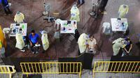 Petugas kesehatan mengumpulkan sampel usap (swab) untuk pengujian COVID-19 dari para pekerja yang siap kembali bekerja di pusat penapisan (screening) regional di Singapura (10/6/2020). (Xinhua/Then Chih Wey)