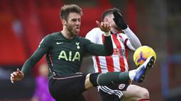 Pemain Tottenham Hotspur, Joe Rodon, berebut bola dengan pemain Sheffield United, Oliver Burke, pada laga Liga Inggris di Stadion Bramall Lane, Minggu (17/1/2021). Tottenham Hotspur menang dengan skor 3-1. (Laurence Griffiths/Pool via AP)