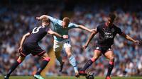 Gelandang Manchester City Kevin De Bruyne (tengah) dikepung duo Huddersfield Town Steve Mounie (kanan) dan Florent Hadergjonaj pada laga di Etihad Stadium, Minggu (6/5/2018). (AFP/Oli Scarff)