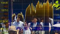 Beberapa orang tercermin dalam papan yang menampilkan indeks pasar saham terbesar di Tokyo, Jepang, Jumat, (10/7/2015). Meskipun Nikkei mengalami kenaikan pada Jumat pagi, tetapi tertutupi oleh penurunan tajam di Fast Retailing Co. (REUTERS/Thomas Peter)