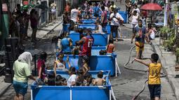 Anak-anak didampingi orang tua bermain di kolam portabel yang diberikan oleh pemerintah setempat untuk mendinginkan tubuh pada saat musim panas di Manila, Filipina (12/4). (AFP Photo/Noel Celis)