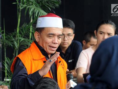 Tersangka Gubernur Aceh Irwandi Yusuf menjawab pertanyaan wartawan usai menjalani pemeriksaan di Gedung KPK, Jakarta, Kamis (26/7). Irwandi Yusuf memakai rompi tahanan dan kopiah merah putih. (Merdeka.com/Dwi Narwoko)
