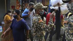 Pejabat kota India mengambil foto warga yang didenda karena tidak memakai masker di pasar yang sibuk di Bengaluru, Minggu (11/4/2021). India melaporkan lonjakan COVID-19 yang menurut para ahli disebabkan oleh mengabaikan aturan jarak sosial serta mengenakan masker di ruang publik. (AP/Aijaz Rahi)