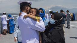 Seorang perwira angkatan laut memeluk seorang anak Upacara Tabur Bunga di geladak heli KRI Dr. Soeharso 990 di perairan utara Pulau Bali, Bali, Jumat (30/4/2021). Upacara itu digelar sebagai penghormatan terakhir bagi awak KRI Nanggala 402 yang gugur dalam medan tugas. (Juni Kriswanto/AFP)