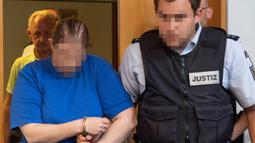 Terdakwa Berrin T (kiri) memasuki ruangan sebelum sidang putusan di pengadilan distrik di Freiburg, Jerman, Selasa (7/8). Berrin dan suami divonis penjara 12 dan 12,5 tahun. (THOMAS KIENZLE/AFP)