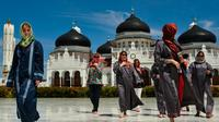Turis asing mengenakan jilbab saat mengunjungi Masjid Agung Baiturrahman di Banda Aceh, Aceh pada 6 Agustus 2019. Selain sebagai tempat ibadah, Masjid Baiturahman juga menjadi tempat wisata bagi turis lokal dan mancanegara. (CHAIDEER MAHYUDDIN / AFP)