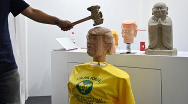 """Seorang pengunjung memukul boneka kayu menyerupai Presiden AS, Donald Trump pada pameran Consumer Electronics Show Asia (CES Asia) di Shanghai, China, 11 Juni 2019. Di tempat ini, mereka bisa memukul kepala Trump sepuasnya dengan palu di kios """"pelepas-stres"""" tersebut. (HECTOR RETAMAL / AFP)"""