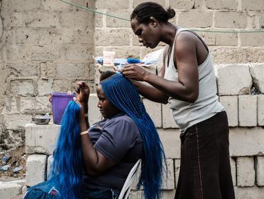 Seorang wanita saat dikepang rambutnya di pemukiman informal Elechi Phase 3 di Port Harcourt, Nigeria selatan (14/2). Nigeria akan mengadakan pemilihan presiden dan parlemen pada tanggal 16 Februari 2019. (AFP Photo/Yasuyoshi Chiba)