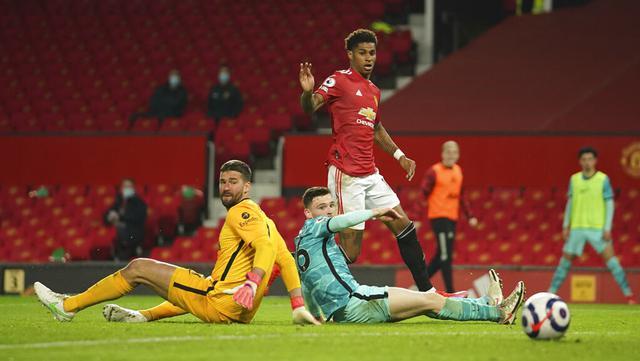 Pemain Manchester United Marcus Rashford (atas) mencetak gol ke gawang Liverpool pada pertandingan Liga Inggris di Stadion Old Trafford, Manchester, Inggris, Kamis (13/5/2021). Liverpool melumat Manchester United 4-2. (AP Photo/Dave Thompson, Pool)