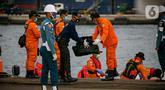 Petugas membawa body part dari kapal Basarnas di JICT II Tanjung Priok, Jakarta, Jumat (15/1/2021).  Badan SAR Nasional (Basarnas) kembali menerima paket kiriman hasil pencarian hari ketujuh. (Liputan.com/Faizal Fanani)
