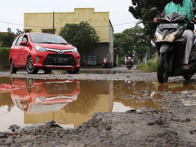 Kendaraan menghindari kubangan pada jalan yang rusak di Jalan Pertamina, Kemiri Muka, Depok, Jawa Barat, Selasa (5/3). Jalan rusak yang telah berlangsung bertahun-tahun tersebut tak kunjung diperbaiki. (Liputan6.com/Immanuel Antonius)