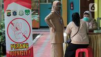 Orangtua murid berkonsultasi terkait pendaftaran daring PPDB tahun ajaran 2021/2022 di Posko Pelayanan PPDB Jakarta Selatan, SMA Negeri 70 Bulungan, Jakarta, Senin (21/6/2021). Pendaftaran PPDB jalur zonasi untuk SMP dan SMA di DKI akan dibuka pada 28 Juni 2021. (Liputan6.com/Herman Zakharia)