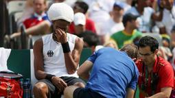 Petenis asal Jerman, Dustin Brown menangis saat tim medis mengobati cidera yang di alaminya saat bertanding di Olimpiade Rio 2016 melawan Thomaz Bellucci asal Brasil, Brasil (7/8). (REUTERS/Kevin Lamarque)