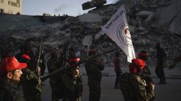 Militan Front Demokratik untuk Pembebasan Palestina (DFLP) berbaris melewati sebuah bangunan yang hancur oleh serangan udara selama parade di jalanan Kota Gaza, Selasa (8/6/2021). Gencatan senjata mengakhiri perang 11 hari antara Hamas sebagai penguasa Gaza dengan Israel. (AP Photo/Felipe Dana)