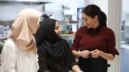 Meghan Markle berbincang dengan anggota komunitas Hubb Community Kitchen di London, Inggris (21/11). Istri Pangeran Harry itu rutin mengikuti kegiatan bersama kelompok Hubb Community Kitchen sejak Januari 2018. (Chris Jackson/Pool via AP)