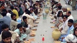 Para peserta buka puasa bersama ini mengaku selain bisa mendapatkan makanan berbuka secara gratis mereka juga bisa menjalin kebersamaan, Pakistan, Quetta, Rabu (2/7/2014) (AFP PHOTO/BANARAS KHAN)