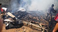 Warga dan petugas bersama sama memadamkan api yang membakar 2 rumah.