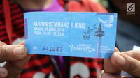"""Warga menunjukkan kupon yang akan ditukarkan sembako gratis dalam acara """"Untukmu Indonesia"""" di lapangan Monas, Jakarta, Sabtu (28/4). (Liputan6.com/Arya Manggala)"""