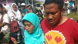 Seorang pria membawa anaknya ke jalan setelah gempa berkekuatan magnitudo 6,8 di desa Batu Merah di Ambon, kepulauan (26/9/2019). Gempa magnitudo 6,8 diikuti gempa susulan magnitudo 5,6. Kemacetan sempat terjadi setelah gempa. (AFP Photo/Yusnita)