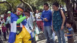 Seorang badut menghibur warga selama parade pada Konvensi Badut Regional ke-5 di kota Guatemala, Rabu (19/9). Dalam acara tersebut, dengan kostum warna-warninya mereka berparade menelusuri jalanan pusat sejarah Guatemala City. (AFP / Johan ORDONEZ)