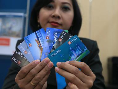 Petugas menunjukkan Kartu Tapcash Bank BNI di Jakarta, Selasa (18/10). Bank Indonesia (BI) menaikkan batas atas plafon uang elektronik menjadi Rp 10 juta yang sebelumnya hanya Rp 5 juta. (Liputan6.com/Angga Yuniar)