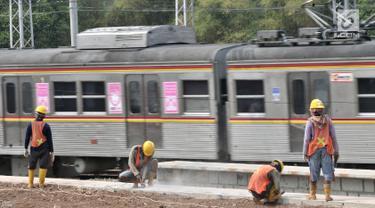 KRL melintas di tengah aktivitas pekerja menyelesaikan proyek Double Double Track (DDT) Paket A Stasiun Manggarai-Jatinegara di Manggarai, Jakarta, Selasa (28/8). Proyek DDT Paket A diperkirakan rampung pada 2020. (Merdeka.com/Iqbal Nugroho)