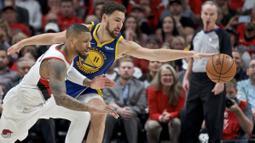 Pebasket Golden State Warriors, Klay Thompson, berebut bola dengan pebasket Portland Trail Blazers, Damian Lillard, pada laga NBA 2019 di Moda Center, Senin, (20/5). Warriors menang 119-117 atas Blazers. (AP/Craig Mitchelldyer)
