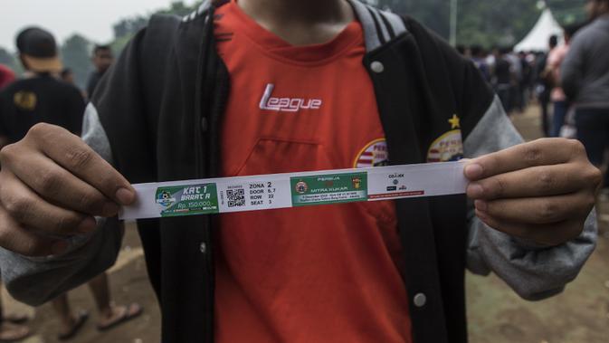 Suporter Persija Jakarta, The Jakmania, menunjukan tiket usai antri untuk menukar tiket di Lapangan Blok S, Jakarta, Minggu (9/12). Persija akan menjalani laga penentuan gelar juara melawan Mitra Kukar. (Bola.com/Vitalis Yogi Trisna)