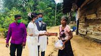 Sepasang pengantin membagikan paket makanan untuk merayakan resepsi di masa pandemi.