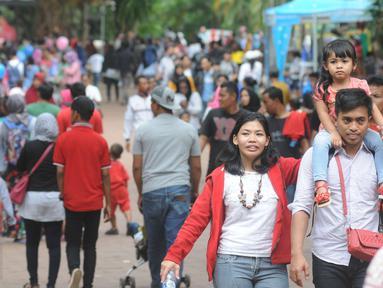 Seorang pengunjung menggendong anaknya saat berkunjung ke Ragunan, Jakarta, Minggu (25/12). Libur Natal dimanfaatkan warga untuk rekreasi bersama keluarga ke Ragunan. (Liputan6.com/Helmi Afandi)
