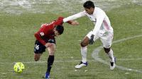 Pemain Osasuna, Jonathan Calleri, berebut dengan pemain Real Madrid, Raphael Varane, pada laga Liga Spanyol di Stadion El Sadar, Sabtu (9/1/2021). Kedua tim bermain imbang 0-0. (AP/Alvaro Barrientos)