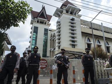 Anggota kepolisian berjaga saat proses penyisiran sebuah gereja di Surabaya menjelang Paskah setelah bom bunuh diri di katedral Makassar, Rabu (31/3/2021). Kegiatan tersebut merupakan upaya peningkatan pengamanan tempat ibadah, khususnya gereja di kota pahlawan. (Juni Kriswanto/AFP)