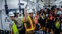 Gubernur DKI Jakarta Anies Baswedan saat mencoba Moda Raya Terpadu (MRT) dari Stasiun Bundaran HI-Lebak Bulus, Jakarta, Senin (10/12). Anies terlihat banyak tersenyum selama perjalanan. (Liputan6.com/Faizal Fanani)