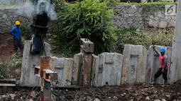 Sejumlah pekerja menyelesaikan pemasangan tanggul dan turap kali di Inspeksi Kali Grogol Palmerah, Jakarta, Rabu (21/11). Normalisasi tersebut dilakukan untuk mengantisipasi banjir dan genangan di Jakarta Barat. (Liputan6.com/Faizal Fanani)