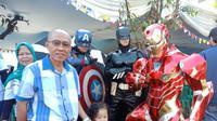 Warga tampak antusias berfoto bersama 2 super hero, yaitu Iron Man, Batman dan Captain America di TPS 21, Kelurahan Cigadung, Kecamatan Cibeunying Kaler, Kota Bandung. (Liputan6.com/Huyogo Simbolon)