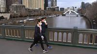 Orang-orang dengan masker berjalan di jembatan yang melintasi Sungai Yarra pada hari pertama wajib masker, di Melbourne Kamis (23/7/2020). Penduduk kota terpadat kedua di Australia, Melbourne, diwajibkan mengenakan masker saat meninggalkan rumah untuk mencegah penyebaran COVID-19. (William WEST/AFP)