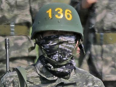 Pemain Tottenham Hotspur, Son Heung-min, berseragam militer lengkap dengan senjata saat mengikuti wajib militer di Korsel, (6/5/2020). Penundaan Premier League karena virus corona dimanfaatkan Son Heung-min untuk mengikuti program wajib militer. (AP/Park Ji-ho)