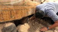 """Menteri Purbakala Mesir Khaled el-Anany memeriksa 20 peti mati kuno terbuat dari kayu yang ditemukan di kota Luxor, 15 Oktober 2019. Kementerian menyebutkan penemuan ini merupakan """"salah satu yang terbesar dan terpenting"""" dalam beberapa tahun terakhir. (Egyptian Ministry of Antiquities via AP)"""