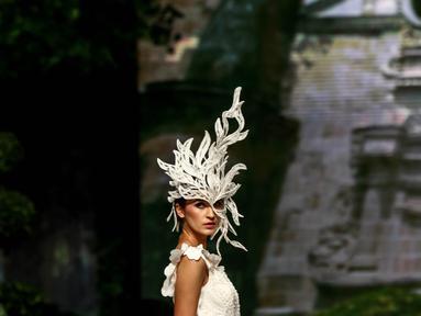 Seorang model dengan menggunakan mahkota berelemen daun atau bunga berjalan saat catwalk pada pagelaran busana tahunan karya desainer Fetty Rusli di Jakarta,  (26/02). Busana bertema A Maze berlangsung megah dan mewah (Liputan6.com/Fery Pradolo)